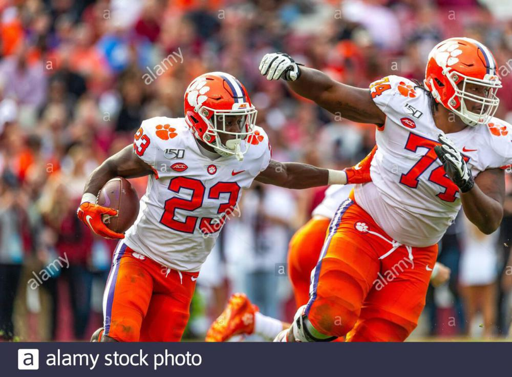columbia-sc-usa-30th-nov-2019-clemson-tigers-running-back-lyn-j-dixon-23-pushes-offensive-lineman-john-simpson-74-as-he-runs-with-the-ball-in-the-ncaa-matchup-at-williams-brice-stadium-in-columbia-sc-scott-kinsercal.jpg